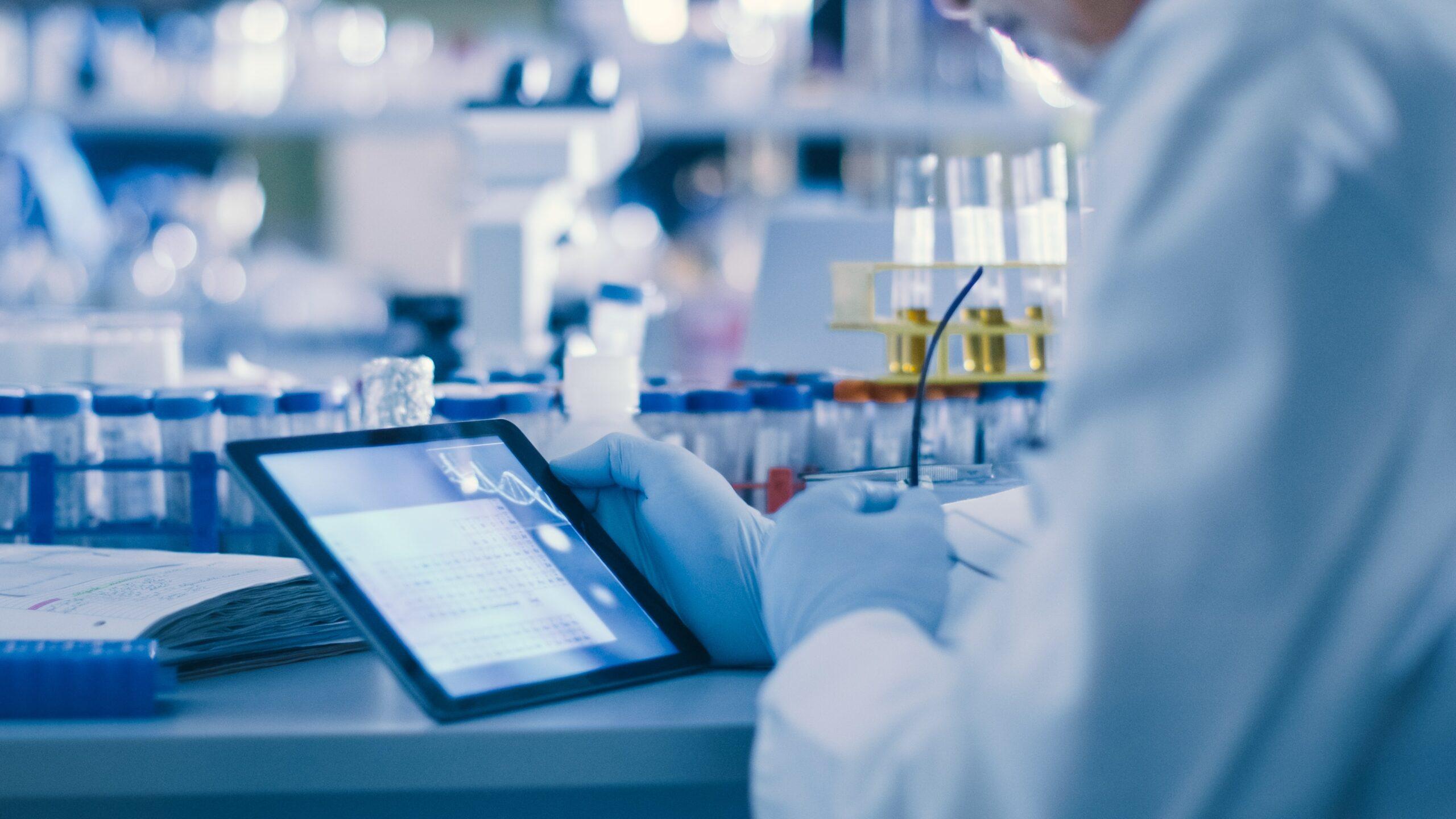 man in lab met handschoenen aan kijkt op ipad