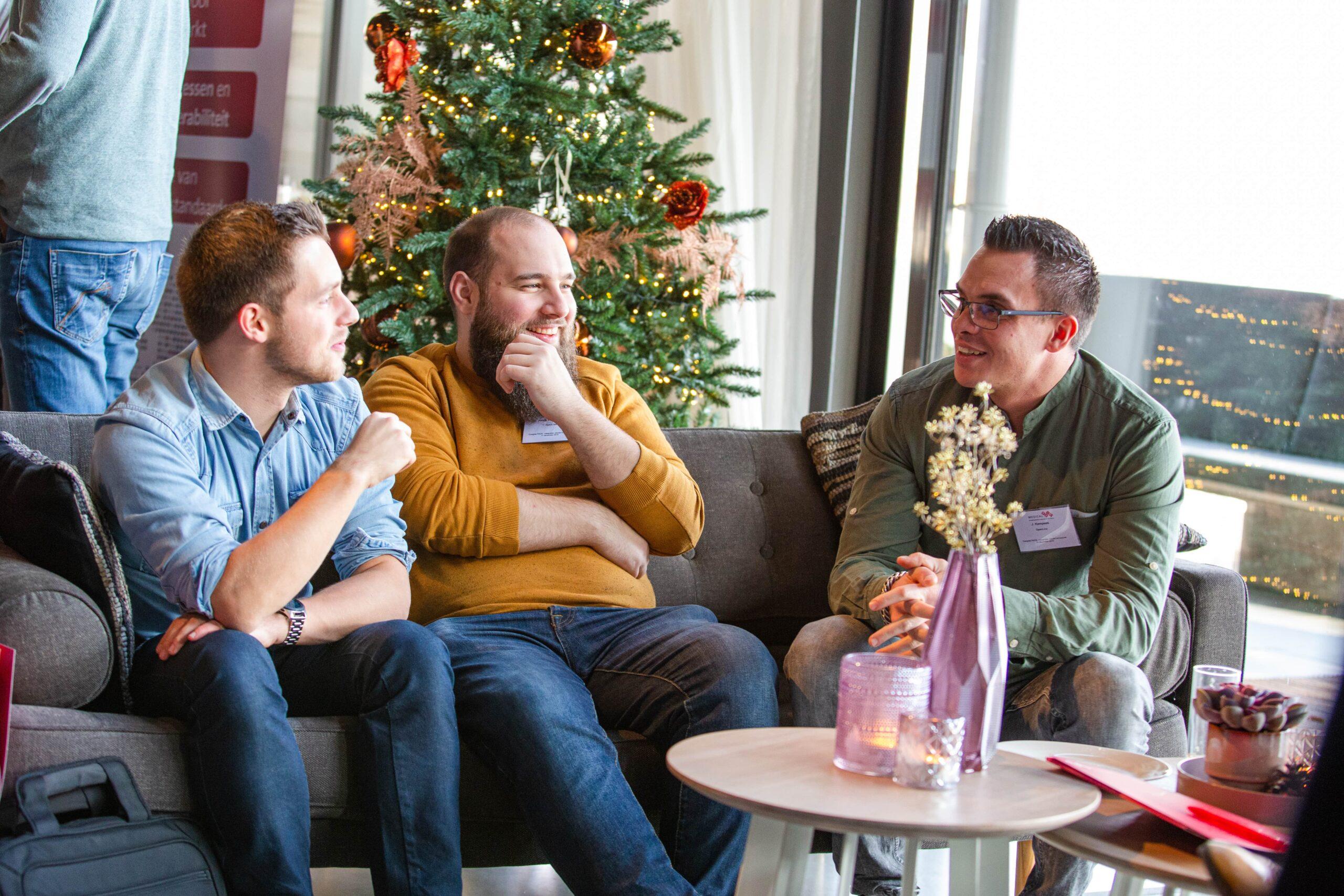 drie mannen zitten op een bank te praten