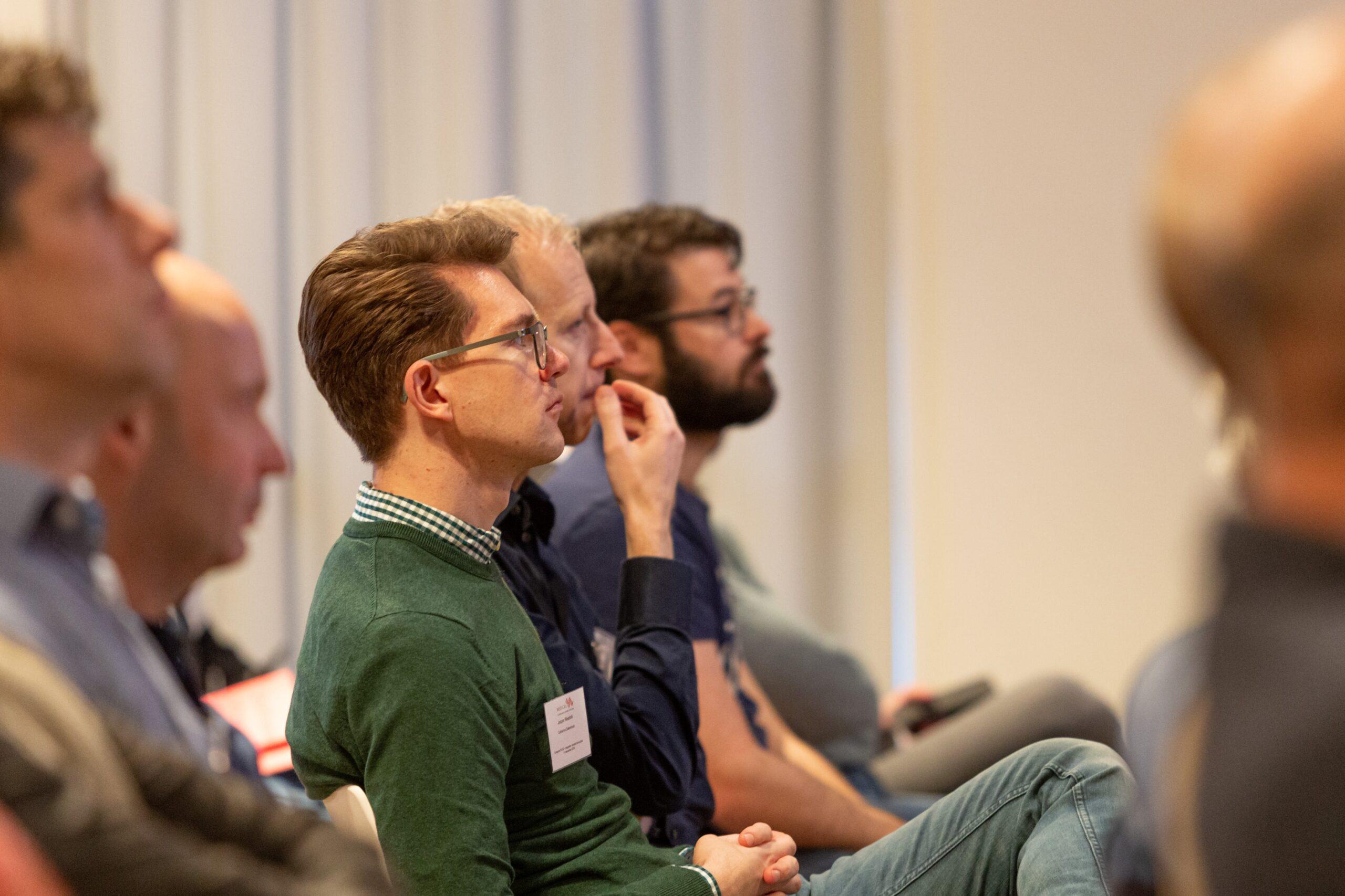 vijf mannen op een rij die luisteren naar een cursusleider